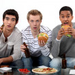 Male friends eating burgers and watching sport on TV - Stock Photo