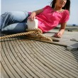 Woman lying on board the deck of a boat — Stock Photo