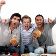 Stock Photo: Friends watching football game together