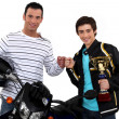 Father congratulating son on motocross victory - Stock Photo