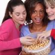 Three young women eating popcorn — Stock Photo