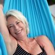 Senior woman laying on a hammock - Stock Photo