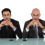 Two businessmen enjoying hamburgers — Stock Photo