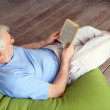 Man on couch reading book — Stock Photo #11847484