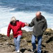Stock Photo: Mature couple walking along a rocky coast