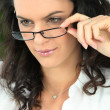 Seductive brunette touching the frame of her glasses — Stock Photo