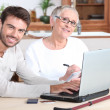 Son helping mother on laptop — Stock Photo #11847682