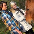 Couple standing by a horse — Stock Photo