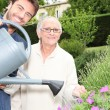 Stock Photo: Young man watering plants with older woman