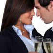 Stock Photo: Flirtatious business couple drinking champagne