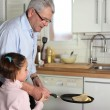Stock Photo: Little girl tossing pancakes with her granddad