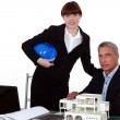 Architects posing with a building model - Stock Photo