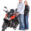 Stock Photo: Couple stood by motorbike