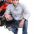 Stock Photo: Man kneeling by motor bike