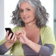 Grey-haired woman sending text message — Stock Photo