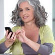 Foto Stock: Grey-haired womsending text message