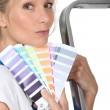 Womstood by ladder holding paint swatches — Stock Photo #11847967