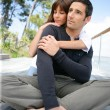Foto Stock: Couple sitting jetty