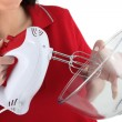 A woman using an electric beater — Stock Photo #11848049