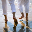 Couple walking barefoot by the sea — Stock Photo