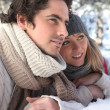 Attractive couple laying in the snow — Stock Photo #11848077