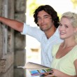 Couple looking at a tourist information board - Stock Photo