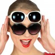 Studio shot of a woman wearing two pairs of sunglasses — Stock Photo #11848307