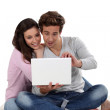 Young couple on sofa with laptop — Stock Photo