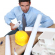 Angry architect sat at his desk - Stock Photo