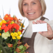 Middle-aged female florist holding out business card — Stock Photo