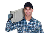 A man carrying a breeze block. — Stock Photo