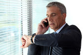 Businessman checking time whist on telephone call — Stock Photo