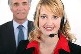 Smart woman wearing a telephone headset — Stockfoto