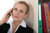 Businesswoman leaning against bookcase during call — Stock Photo