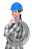 Tradeswoman carrying corrugated tubing — Stock Photo