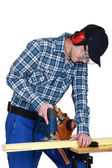 Woodworker using jigsaw — Stock Photo
