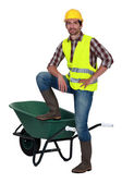 Man casually stood by empty wheelbarrow — Stock Photo
