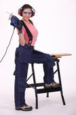 A female carpenter with a jigsaw. — Stock Photo