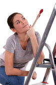 Woman with paint brush leaning on ladder — Stock Photo
