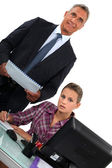 Smiling businessman standing over his overworked assistant — Stock Photo