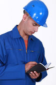 Tradesman writing in his agenda — Stock Photo