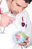 Doctor with syringe and globe — Stock Photo
