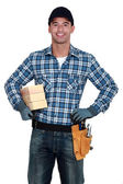 Smiling manual worker with wood — Stock Photo