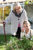 Elderly woman in a garden with a young helper — Stock Photo