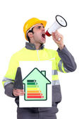 Man with energy rating poster shouting into megaphone — Stock Photo