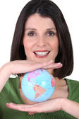 Woman holding a mini-globe between her hands — Stock Photo