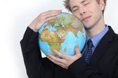Businessman hugging globe — Stock Photo