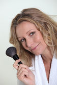 Woman holding blusher brush — Stockfoto