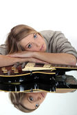 A cute blond resting over a guitar. — Stock Photo