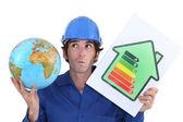 Artesano sosteniendo una etiqueta de consumo de energía y un globo — Foto de Stock